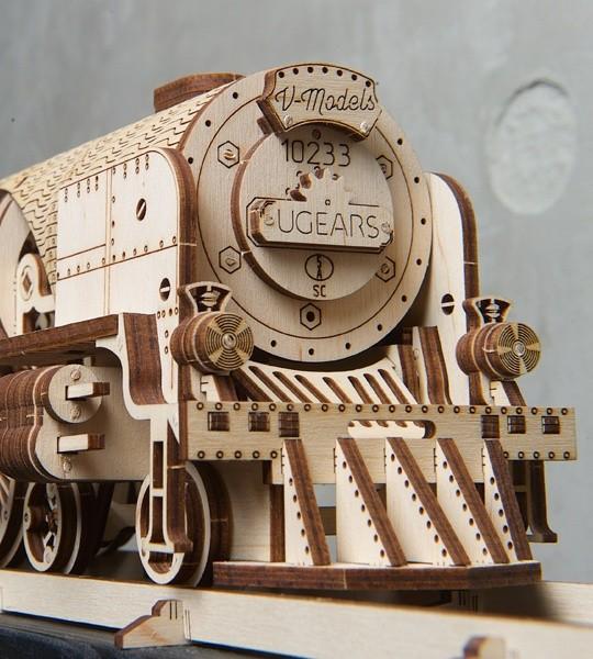 Ugears kit de modelo mecánico Locomotora  de Vapor V-Express con Tender y rompecabezas de madera en 3D para el autoensamblaje. Modelo de locomotora con engranajes y volante, el trabajo de disposición cilindro-pistón - los principales bloques mecánicos de una máquina de vapor real. Regalo original para niños y niñas y afición inteligente para adultos.